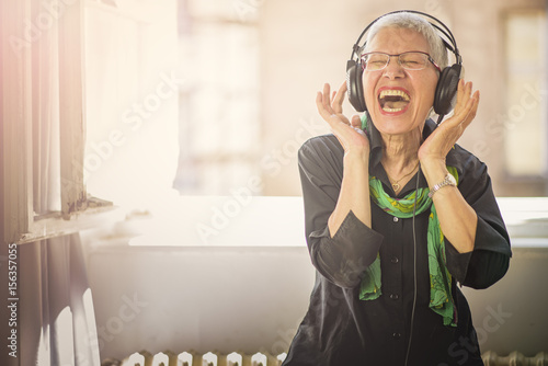 Photo  Senior old woman listening to her favourite music through big headphones, enjoyi