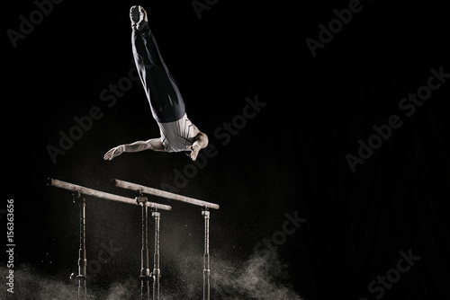 Male athlete performing difficult exercise on gymnastic parallel bars with talcum powder. Isolated on black.