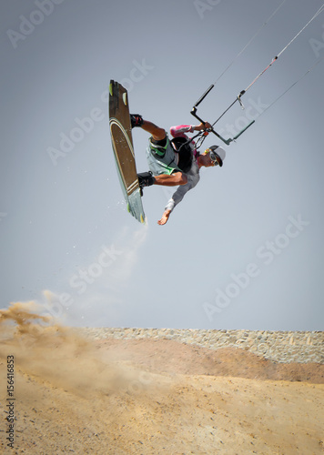 Kiter rides across the land. Professional kite boarding sportsman slides with board in desert sands and stones, extreme sport. Recreational activity and extreme active water sports, hobby and fun time