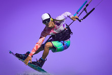 Kite Rider Close Up Portrait. Professional Kite Boarding Rider Sportsman With Kite In Sky Jumps High Acrobatics Kiteboarding Air Trick With Grab Of Kiteboard And Huge Water Splash. Active Water Sport