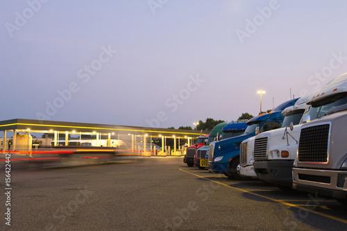 Obraz na plátně  Evening truck stop lights of number of trucks in parking