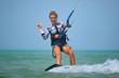 Kite surfing girl in sexy swimsuit with kite in sky on kiteboard in the blue sea riding waves saying hi. Recreational activity, water sports, action, hobby and fun in summer time. Kiteboarding sport