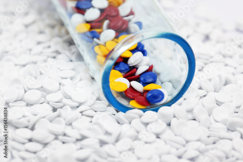 Fotografía  close up of colorful plastic polymer granules in test tube on white