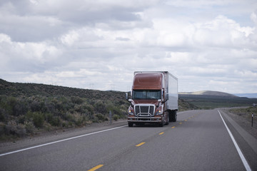 Brown modern semi truck with trailer driving long Nevada highway