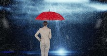 Rear View Of Businesswoman Holding Red Umbrella Standing In Rain