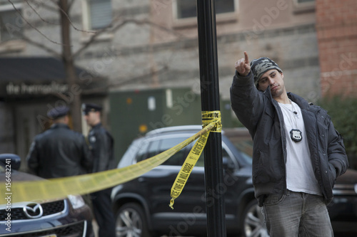 A plainclothes police officer gestures at a crime scene related to