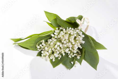 Wall Murals Lily of the valley A bouquet of lilies of the valley bandaged with a pink ribbon on a white wooden table