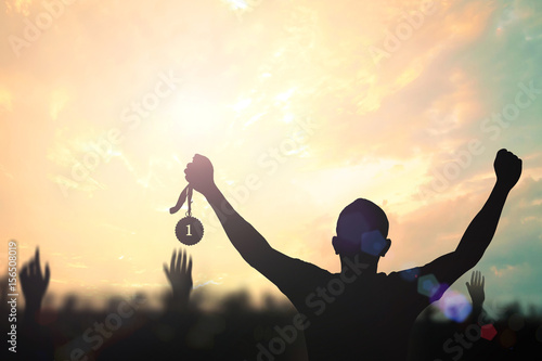 Victory concept: Silhouette human hand holding gold medal against colorful sunset sky Fototapeta