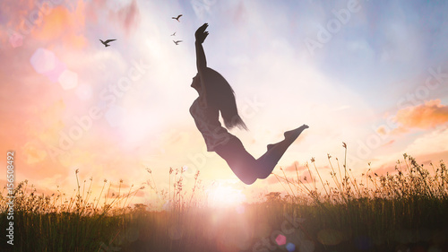 Leinwand Poster World mental health day concept: Silhouette of a girl jumping at autumn sunset m