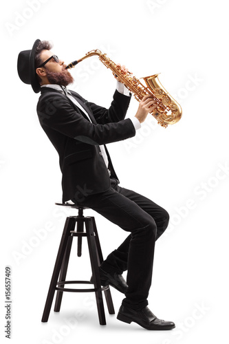 Jazz musician seated on a chair playing a saxophone - 156557409
