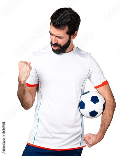 Lucky football player holding a soccer ball