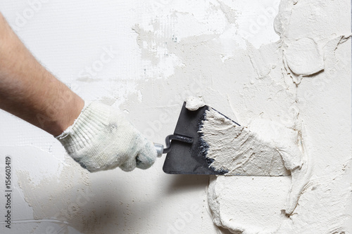 Construction worker puts a gypsum on the wall with a spatula