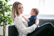 Leinwanddruck Bild - Happy young mother with baby girl on sofa at home