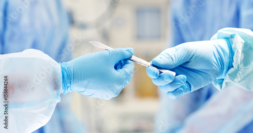 Foto close up of hands with scalpel at operation