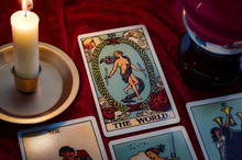 The World Tarot Card And Crystal Ball Under Candle Light. Cartomancy Is Fortune Telling Using Cards, While Scrying And Clairvoyance Is Future Reading Using Orbs, Both Are Branches Of Astrology