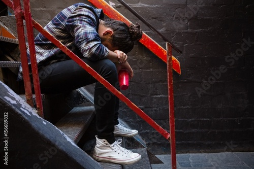 Fotografija  Drunk man sitting on staircase
