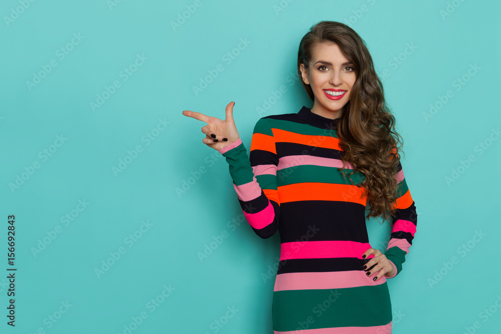 Fototapety, obrazy: Smiling beautiful young woman in colorful vibrant striped dress is posing with hand on hip, pointing and looking at camera. Three quarter length studio shot on turquoise background.