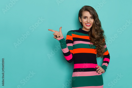 Fotografie, Obraz  Smiling beautiful young woman in colorful vibrant striped dress is posing with hand on hip, pointing and looking at camera