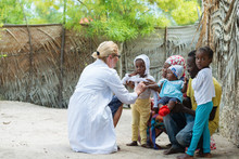Caucasian Female Doctor Listening Heart Beat And Breathing Of Little African Girl , Family Looking Medical Exam