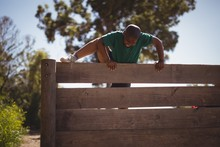 Boy Climbing Wooden Wall During Obstacle Course