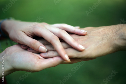 Fotografia  Young couple holding hands; love concept; selective focus background