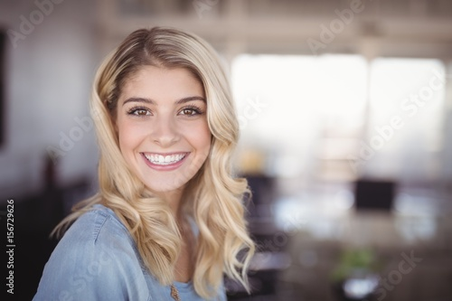 Smiling business woman standing in creative office