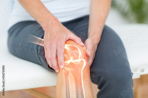 Fotografiet  Mid section of man suffering with knee cramp