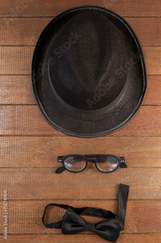 Poster de jardin Vache Hat, spectacles and bow tie arranged on wooden background