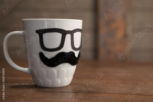 Fake moustache and spectacles on mug