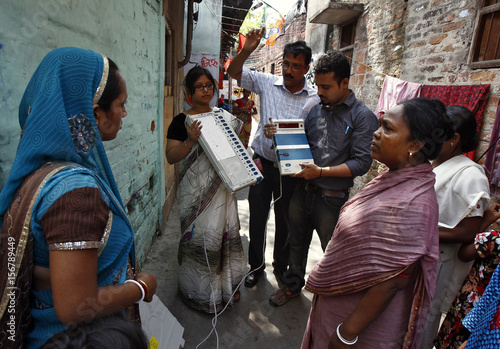 Polling officials demonstrate to residents how to use