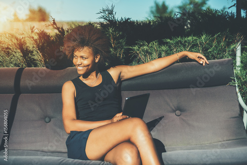 Lovely young afro american female student is sitting on soft swing, holding digi Canvas-taulu