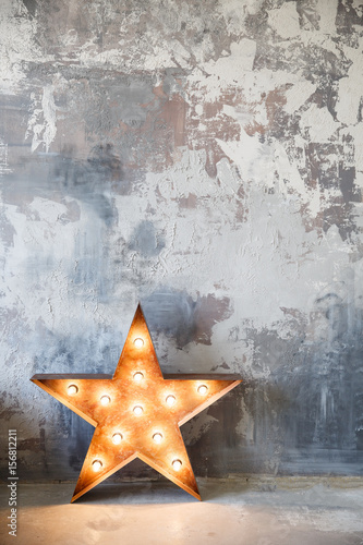 metal star with lamps near gray plaster wall in studio
