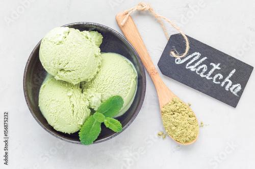 Photo  Matcha green tea ice cream balls in black bowl, horizontal, top view