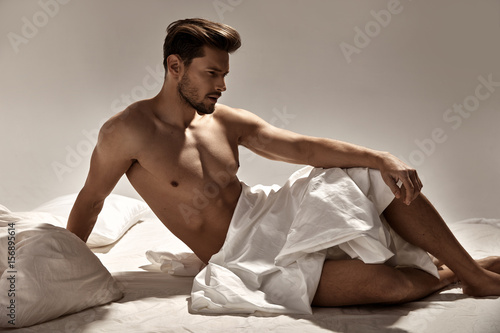 Poster Artist KB Handsome, muscular man posing on the soft bed