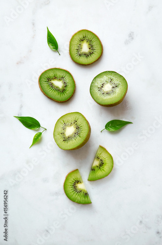 Kiwis flat lay on a marble background. Group of sliced and whole kiwi fruits viewed from above. Top view