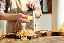 Woman Grating Cheese On Wooden...
