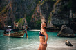 Young tan model on the Maya beach posing wearing bikini with clear water and mountain background, Phi Phi, Thailand