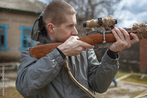 Photo  The man looks in a weapon sight
