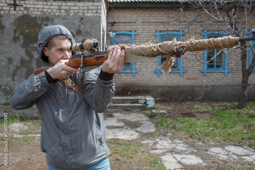 Fotografia  The man looks in a weapon sight