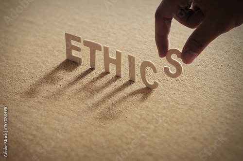 Fotografie, Obraz  ETHICS wood word on compressed board with human's finger at S letter