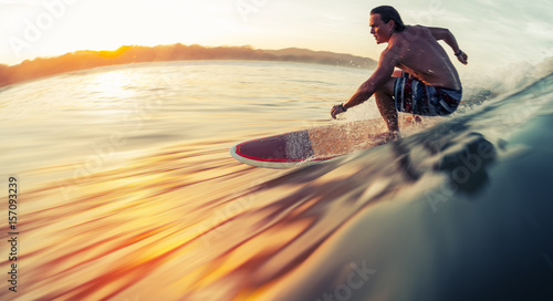 Photo  Surfer rides the ocean wave at sunrise