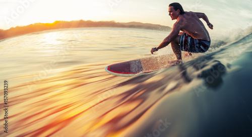 Canvas Print Surfer rides the ocean wave at sunrise