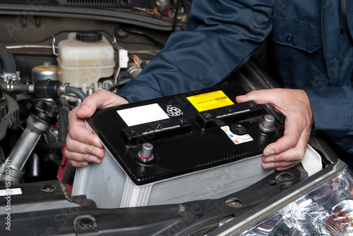Auto mechanic replacing car battery Fotobehang