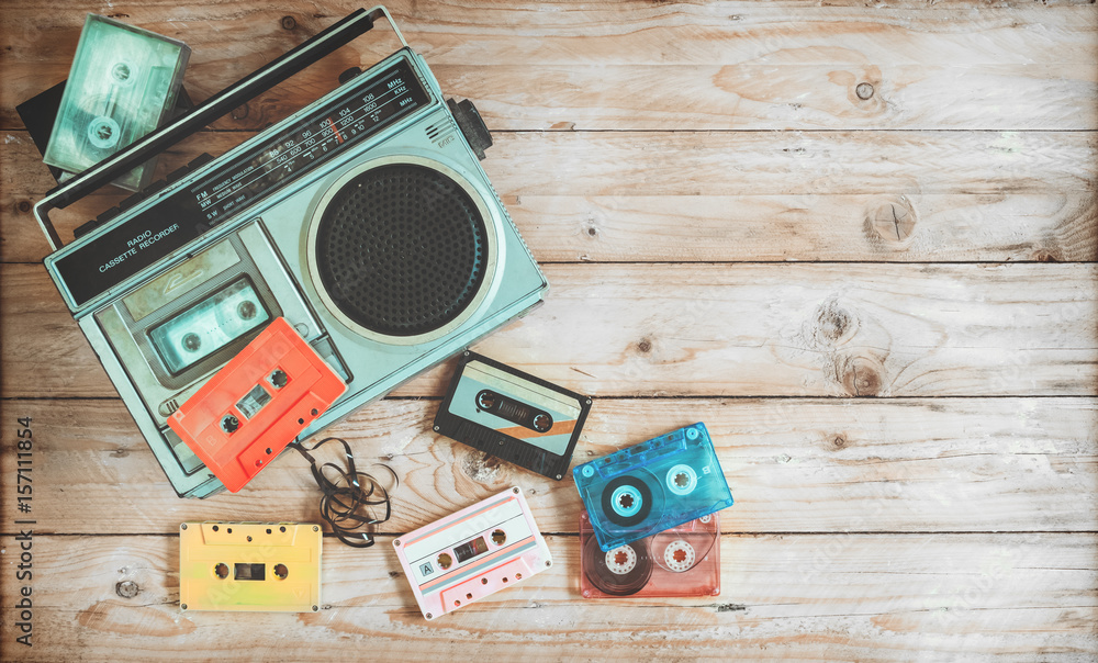Fototapeta Top view hero header - retro technology of radio cassette recorder music with retro tape cassette on wood table. Vintage color effect styles.