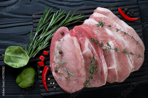 Valokuva  Top view of raw fresh pork loin steaks with seasonings on a black wooden backgro