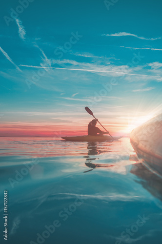 Fotografia, Obraz side view on kayak with another kayaker in the sunset