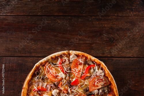 Staande foto Pizzeria Fresh tasty pizza served on rustic wooden table, flat lay. Traditional italian cuisine, pizzeria menu photo. Dark background with free space.