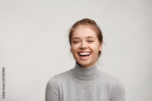 Fotografie, Obraz  Headshot of good-looking lucky woman with tied hair pure skin and broad smile being happy to watch at camera