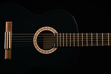 A Black Six-string Classical Acoustic Guitar Isolated On Black Background.