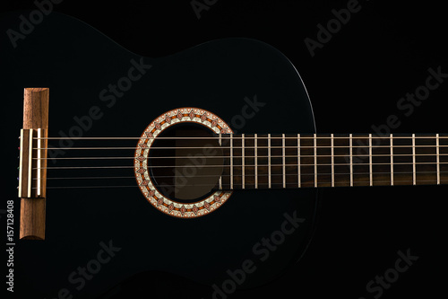 A Black Six String Classical Acoustic Guitar Isolated On Black